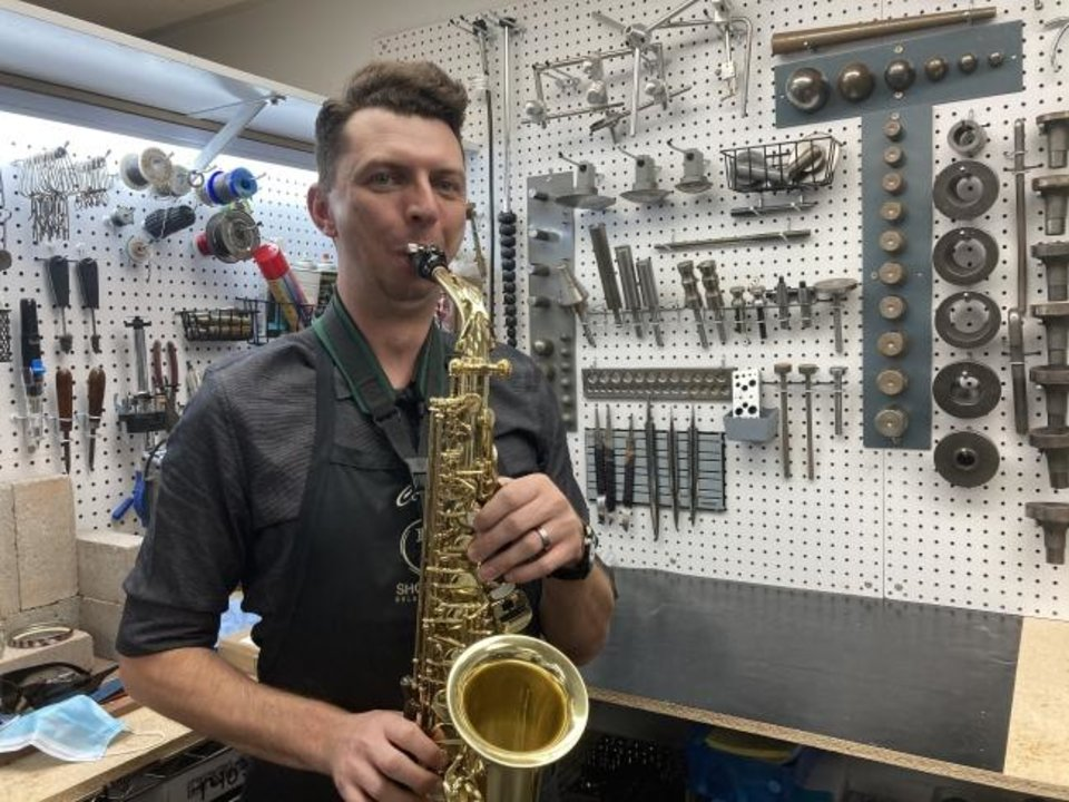 Photo -  Repair technician Colter Weatherholtz tries out an alto sax brought in to Larsen Music for repairs. [KIMBERLY BURK]