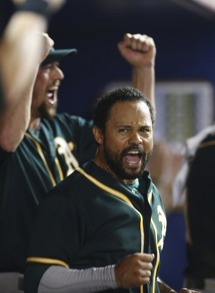 Photo - Oakland Athletics player Coco Crisp reacts after a video review showed he scored the go-ahead run during the ninth inning of a baseball game in Miami against the Miami Marlins, Friday, June 27, 2014. The A's won 9-5. (AP Photo/J Pat Carter)