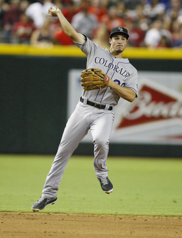 Colorado Rockies third baseman Nolan Arenado  makes the off balance throw against the Arizona Diamondbacks in the third inning during a baseball game on Saturday, July 6, 2013, in Phoenix. (AP Photo/Rick Scuteri)