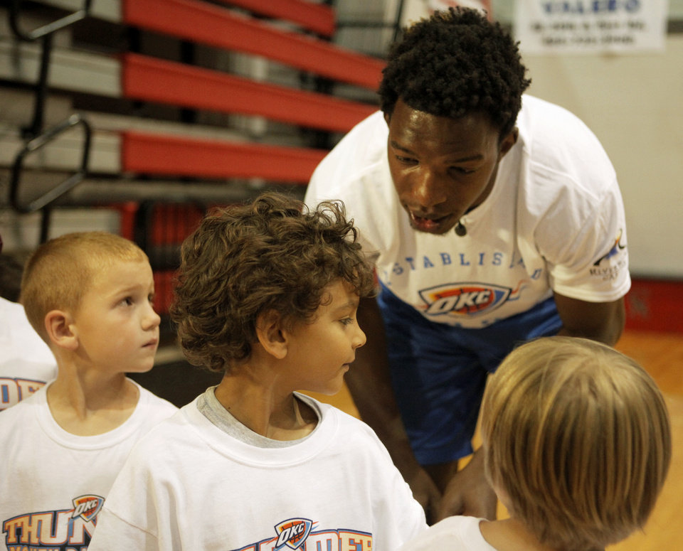 Photo - Hasheem Thabeet, center for the Oklahoma City Thunder, talks to Jay Kakani, 6 of Oklahoma City, before he autographs his shirt at the Thunder basketball camp at Carl Albert High School in Midwest City on June 25, 2013. Photo by KT KING, The Oklahoman