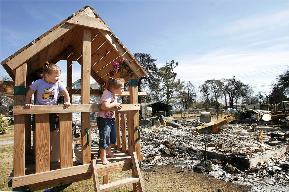 Sisters Sara, 3, and Cheyann Ford, 5, play Tuesday on a wooden swing set that escaped last week's flames. The girls were visiting their grandmother, who lives next door to the burned house in the background.  FEMA officials toured neighborhoods devastated in Thursday's wildfires. PHOTO BY JIM BECKEL, THE OKLAHOMAN