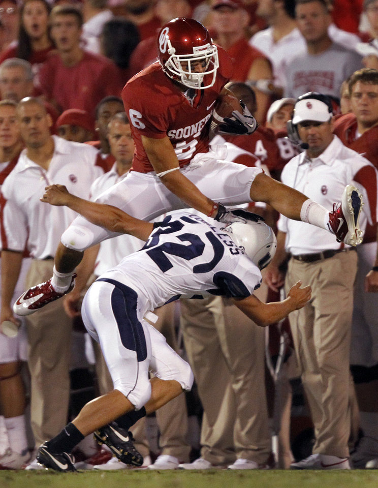 Photo - Oklahoma's Cameron Kenney (6) leaps over Utah State's Braeden Loveless (32) on a kick return during the second half of the college football game between the University of Oklahoma Sooners (OU) and Utah State University Aggies (USU) at the Gaylord Family-Oklahoma Memorial Stadium on Saturday, Sept. 4, 2010, in Norman, Okla.   Photo by Chris Landsberger, The Oklahoman
