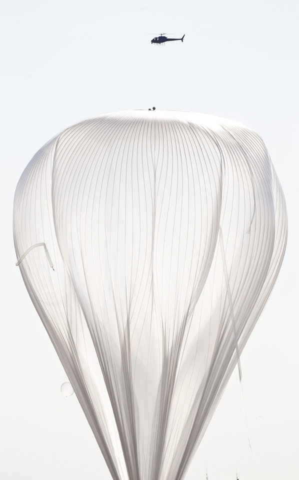 A helicopter hovers above the helium balloon, attached to the capsule carrying Felix Baumgartner, before he attempts to break the speed of sound with his own body by jumping from the space capsule, Sunday, Oct. 14, 2012, in Roswell, N.M.  Baumgartner plans to jump from an altitude of 120,000 feet, an altitude chosen to enable him to achieve Mach 1 in free fall, which would deliver scientific data to the aerospace community about human survival from high altitudes. (AP Photo/Ross D. Franklin) ORG XMIT: NMRF114