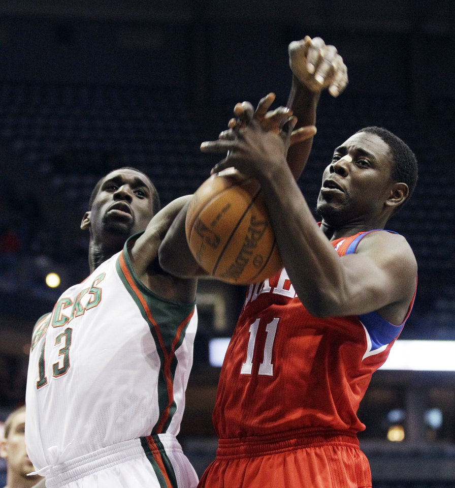 Photo -   Philadelphia 76ers' Jrue Holiday and Milwaukee Bucks' Ekpe Udoh (13) compete for a rebound during the first half of an NBA basketball game, Wednesday, April 25, 2012, in Milwaukee. (AP Photo/Morry Gash)