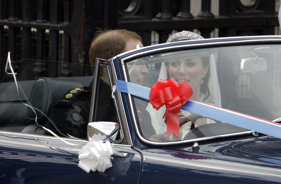 Photo - Britain's Prince William and his wife Kate, Duchess of Cambridge drive away from Buckingham Palace in a convertible after the Royal Wedding in London Friday, April, 29, 2011. (AP Photo/Matt Dunham) ORG XMIT: RWMG211