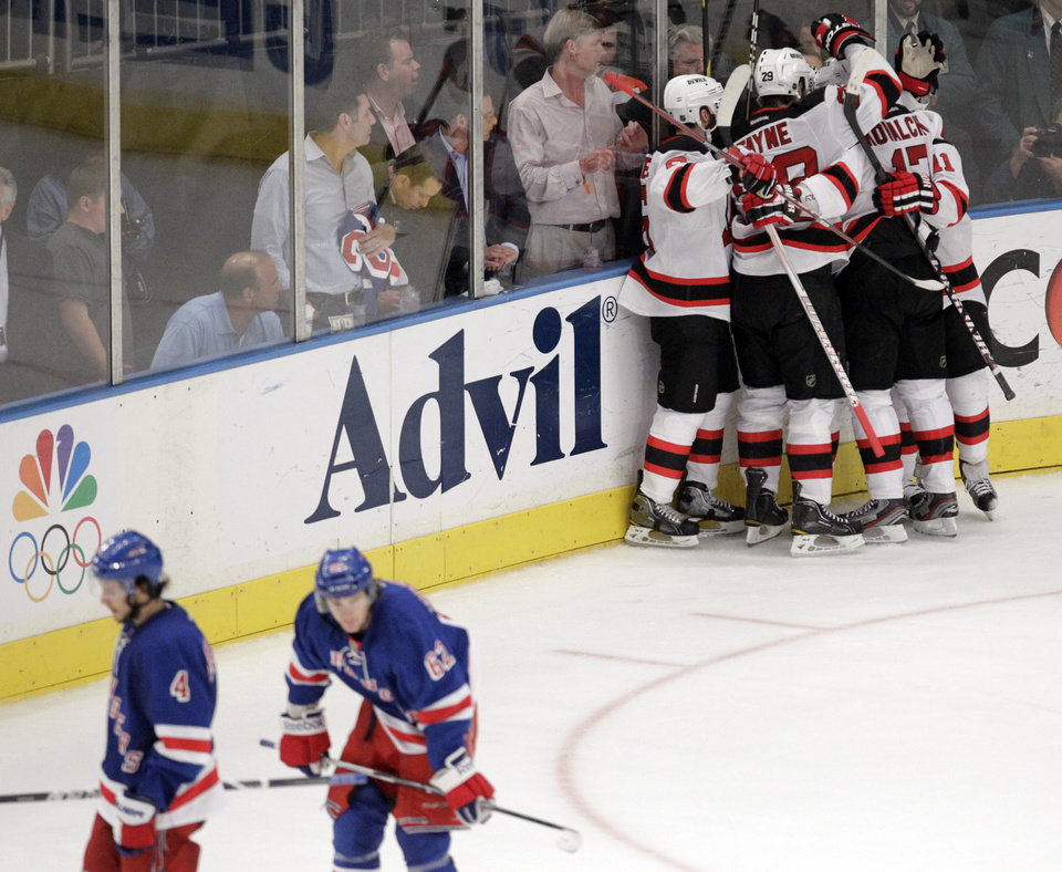 Photo -   Members of the New Jersey Devils celebrate a goal by Ryan Carter against the New York Rangers during the third period of Game 5 of an NHL hockey Stanley Cup Eastern Conference final playoff series, Wednesday, May 23, 2012, in New York. The Devils won 5-3. (AP Photo/Julio Cortez)