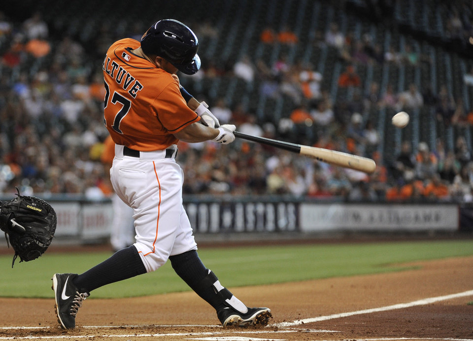 Photo - Houston Astros' Jose Altuve connects for a single against the Chicago White Sox in the first inning of a baseball game, Friday, June 14, 2013, in Houston. (AP Photo/Pat Sullivan)