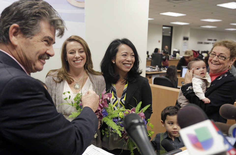 Photo - Cook County Clerk David Orr, left, performs a marriage ceremony for Theresa Volpe, second from left, and Mercedes Santos on Friday, Feb. 21, 2014, in Chicago. Same-sex couples in Illinois' Cook County began receiving marriage licenses immediately after a federal judge's ruling Friday that some attorneys could give county clerks statewide justification to also issue the documents right away. (AP Photo/M. Spencer Green)