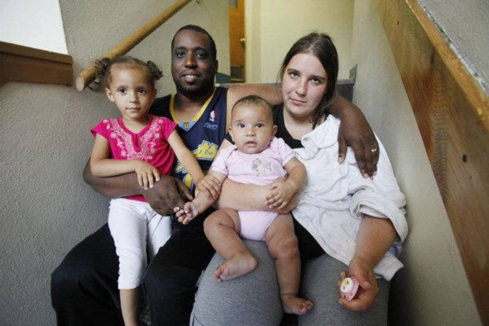 Photo - U.S. Army veteran Gary Matthews and his wife, Raffaela, pose with their daughters, Larissa, 2, and Chiara, 4 months. The family currently lives at the Salvation Army shelter.  Steve Gooch