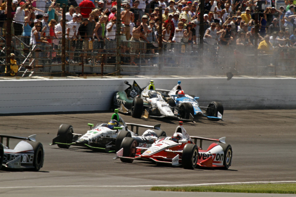Photo - Ed Carpenter (20) and James Hinchcliffe, (27) of Canada, crash in the first turn during the 98th running of the Indianapolis 500 IndyCar auto race at the Indianapolis Motor Speedway in Indianapolis, Sunday, May 25, 2014. (AP Photo/Steve Metz)