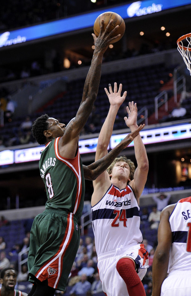 Milwaukee Bucks center Larry Sanders (8) goes to the basket against Washington Wizards forward Jan Vesely (24), of the Czech Republic, during the first half of an NBA basketball game on Friday, Nov. 9, 2012, in Washington. (AP Photo/Nick Wass)