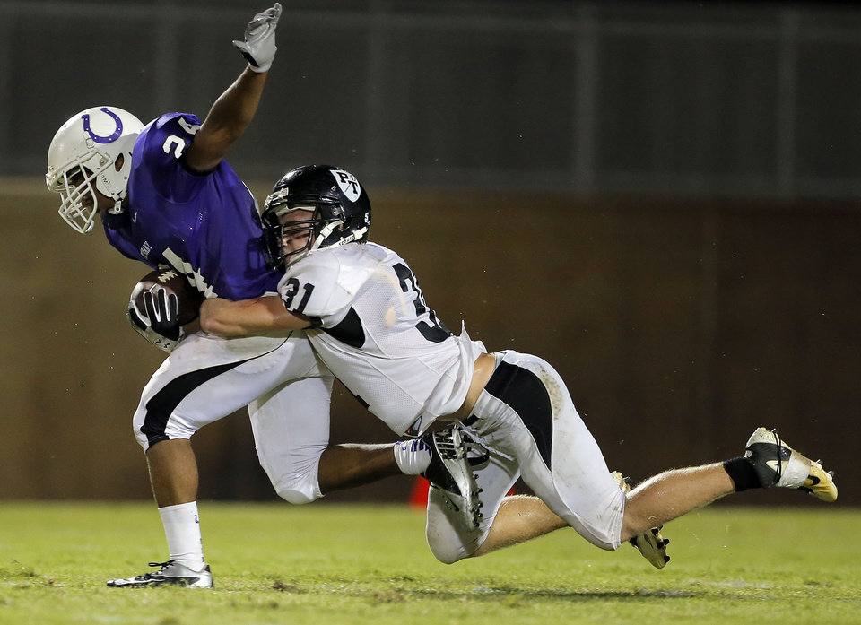 Photo - Bethany's Dorien Jackson is brought down by Perkins' Clark Crotty during the high school football game between Bethany High School and Perkins in Bethany, Okla., Friday, Sept. 28, 2012.  Photo by Sarah Phipps, The Oklahoman