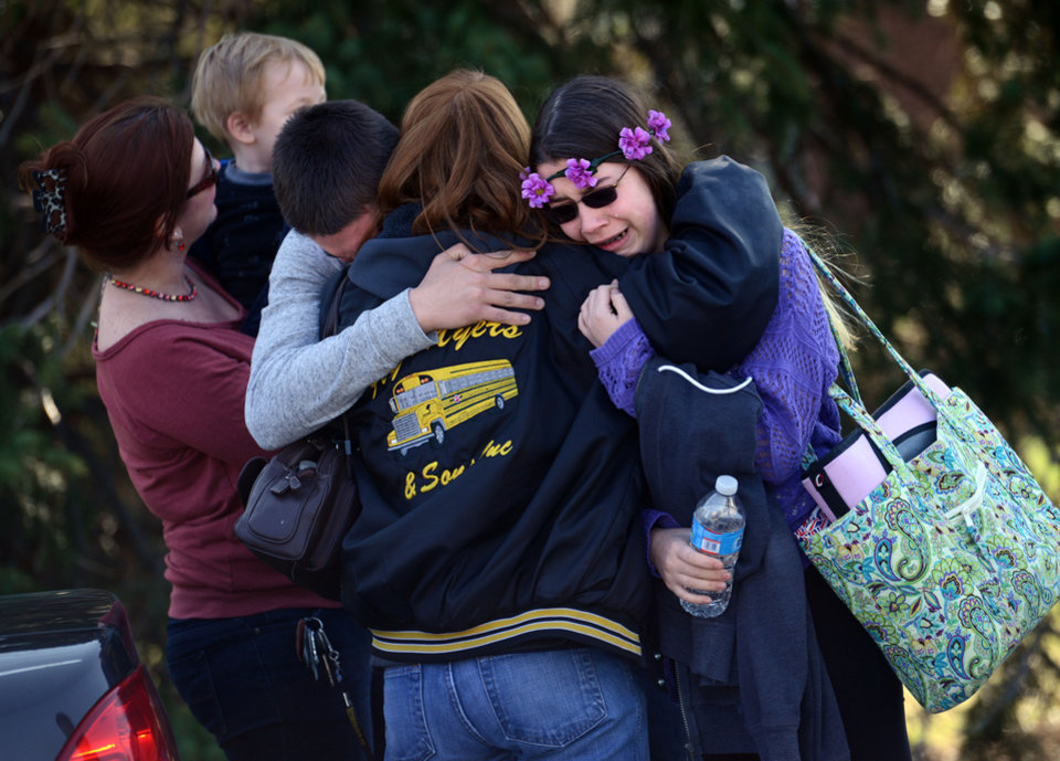 Photo - Parents and students embrace along School Road near Franklin Regional High School after more than a dozen students were stabbed by a knife wielding suspect at the school on Wednesday, April 9, 2014, in Murrysville, Pa., near Pittsburgh. The suspect, a male student, was taken into custody and is being questioned. (AP Photo/Tribune Review, Sean Stipp)  PITTSBURGH OUT