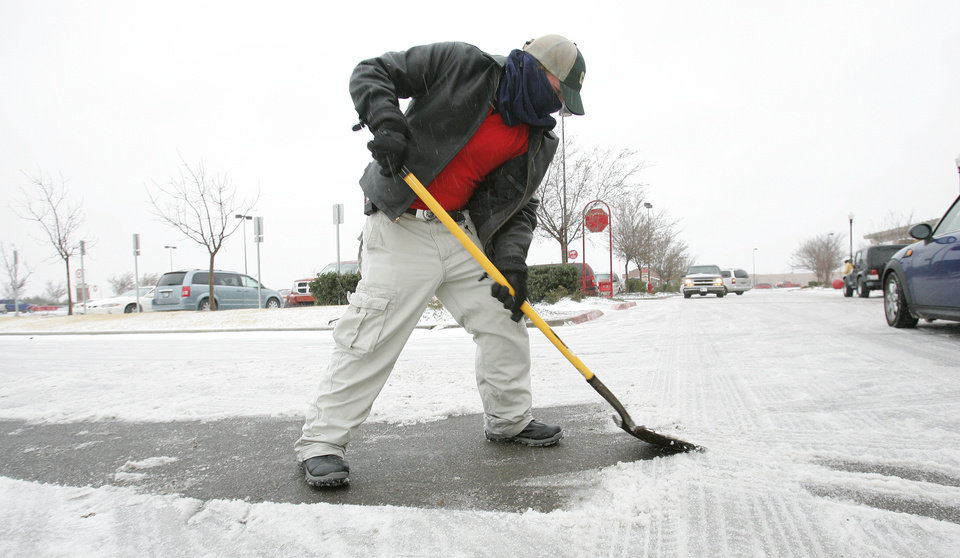 Photo - Target team member Brady Curry of Norman shovels a path outside the Norman Target Thurs. Dec. 24, 2009. Photo by Jaconna Aguirre, The Oklahoman.