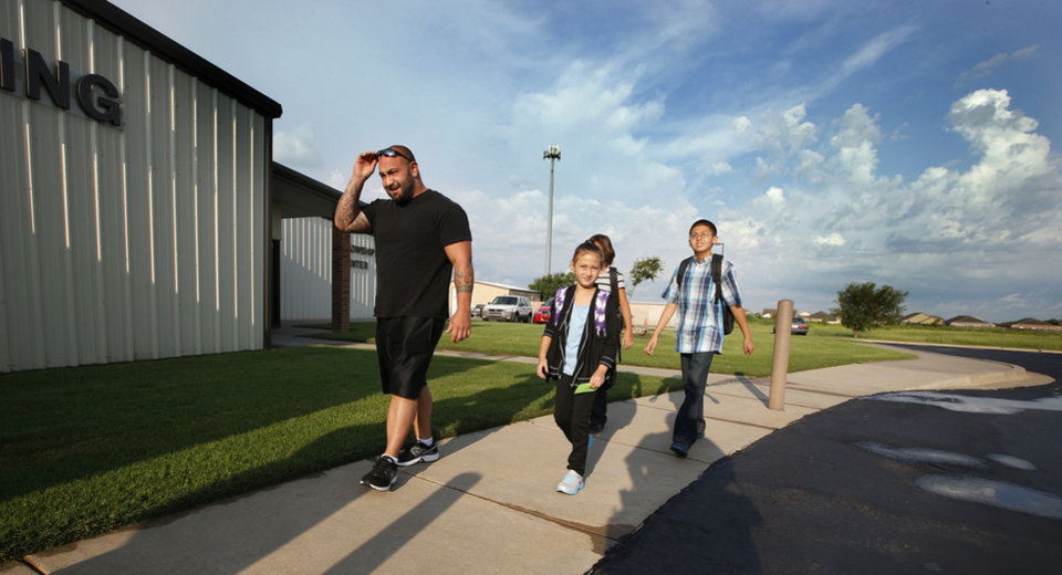 Photo - Roger Barrow walks Isabell, Alex, and Josh Inauen to school for the first day of class at Briarwood Elementary School on Friday, Aug. 16, 2013 in Moore, Okla.  The school was heavily damaged by the May 20 tornado and forced to relocate for 2013-2014 school year.  Photo by Steve Sisney, The Oklahoman  STEVE SISNEY