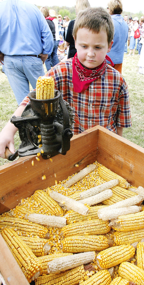 Photo - Josh Bruza, 9, tries out a corn shucker as third-graders from Chisholm Elementary School participate in '89er Day activities. PHOTO BY PAUL B. SOUTHERLAND, THE OKLAHOMAN