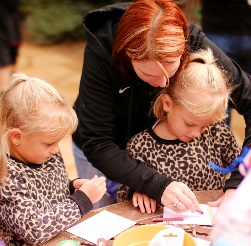 Photo -  DeAndra Williams assists her 5-year-old twins Brenlee, left, and Raylynn, as they craft a spider. [Photo by Doug Hoke, The Oklahoman]