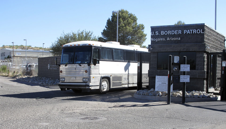 Photo - A bus leaves the entrance of the U. S. Border Patrol facility on Saturday, June 7, 2014 in Nogales, Ariz. Arizona officials said they are rushing federal supplies to this makeshift holding center in the southern part of the state that's housing hundreds of migrant children and is running low on the basics. (AP Photo/Brian Skoloff)