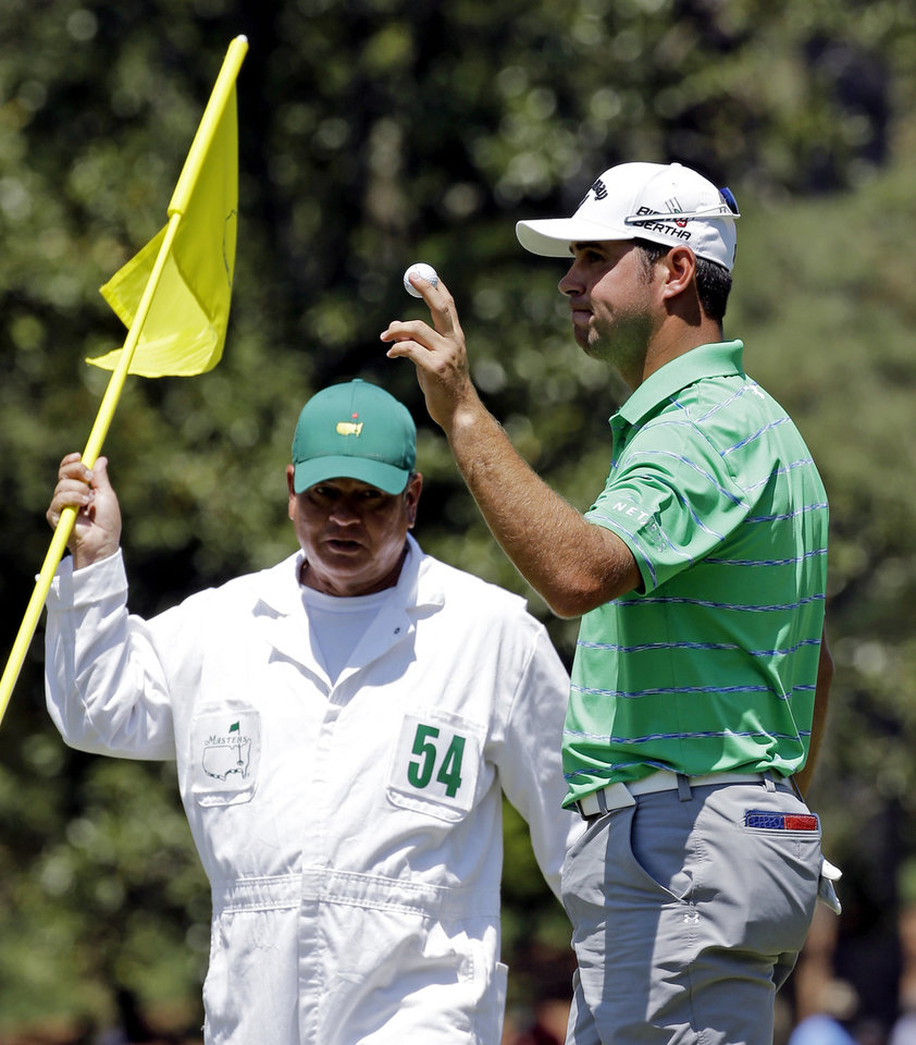 Photo - Caddie Tony Navarro looks at Gary Woodland as he holds up his ball after a birdie on the 10th hole during the third round of the Masters golf tournament Saturday, April 12, 2014, in Augusta, Ga. (AP Photo/David J. Phillip)