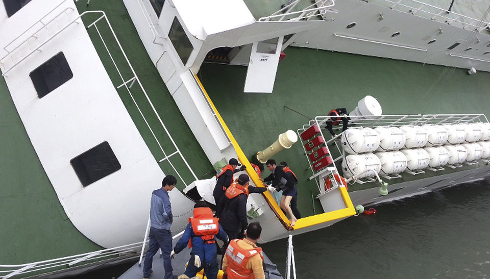 Photo - In this April 16, 2014 photo released by South Korea Coast Guard via Yonhap News Agency, South Korean coast guard officers rescue South Korean ferry Sewol Capt. Lee Joon-seok, wearing a sweater and underwear, from the ferry in the water off the southern coast near Jindo, South Korea. Prosecutors indicted the captain of the sunken ferry and three crew members on homicide charges Thursday, May 15, alleging they were negligent and failed to protect more than 300 people missing or dead in the disaster. Less serious indictments were issued against the 11 other crew members responsible for navigating the vessel. (AP Photo/South Korea Coast Guard via Yonhap) KOREA OUT