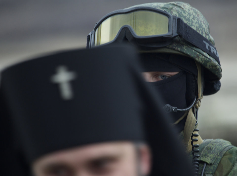 Photo - Russian solder is seen behind Ukrainian Orthodox Archbishop Clement, foreground, outside of a Ukrainian military base in the village of Perevalne, outside of Simferopol, Ukraine, on Sunday, March 2, 2014. Hundreds of armed men in trucks and armored vehicles surrounded the Ukrainian military base Sunday in Crimea, blocking its soldiers from leaving. (AP Photo/Ivan Sekretarev)
