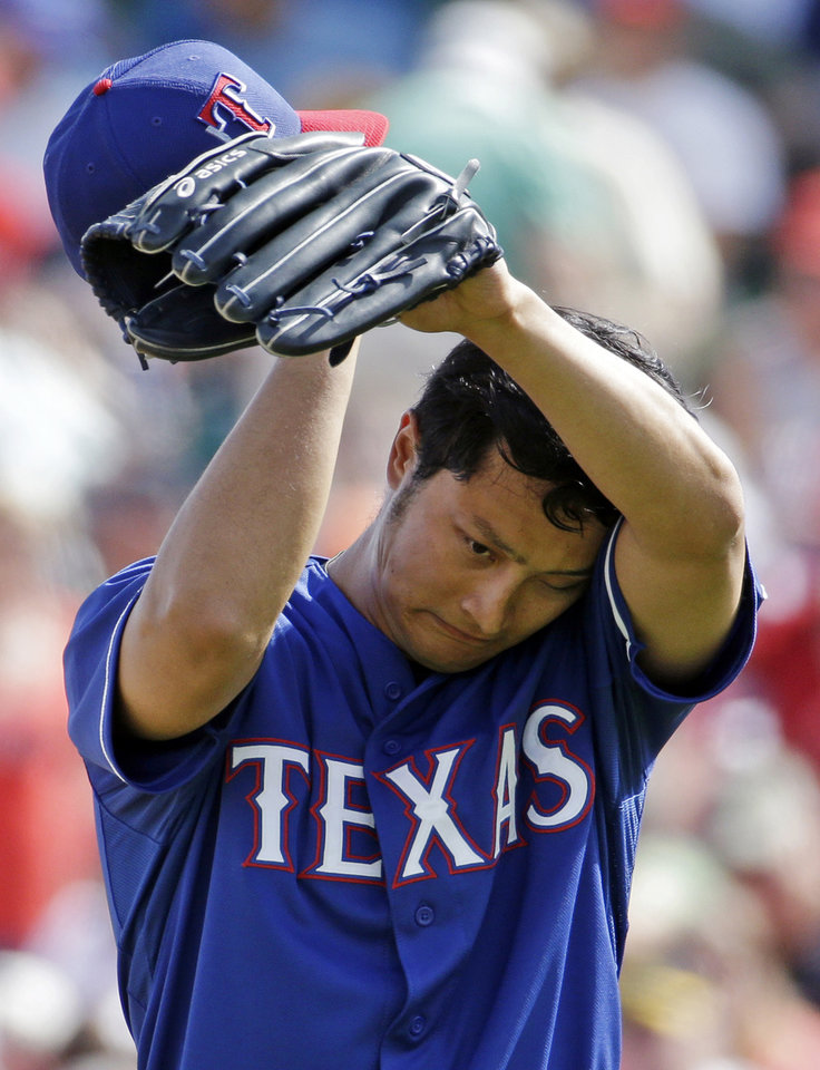 Photo - Texas Rangers' Yu Darvish wipes his face as he heads to the dugout after the second inning of an exhibition spring training baseball game against the Los Angeles Angels, Tuesday, March 4, 2014, in Tempe, Ariz. The Angels scored two runs in the inning. (AP Photo/Morry Gash)