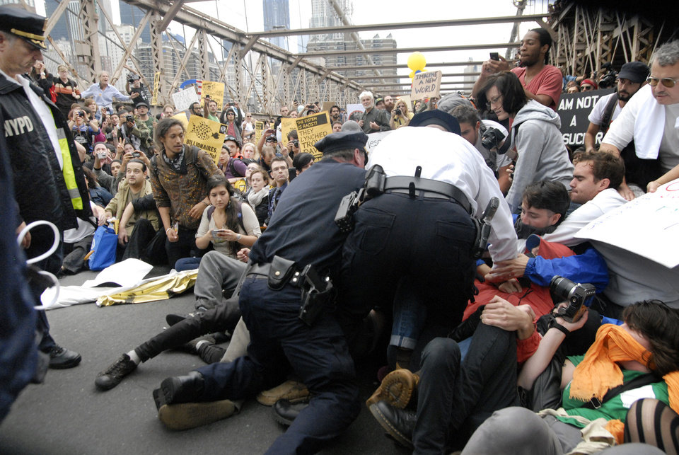 Photo -   FILE - In this Oct. 1, 2011 file photo, police arrest protesters on New York's Brooklyn Bridge during march by Occupy Wall Street. A judge said in a ruling released Monday, July 2, 2012 that Twitter must give a court almost three months' worth of an Occupy Wall Street protester's tweets after prosecutors demand the messages to make a case for arrests. (AP Photo/Stephanie Keith, File)