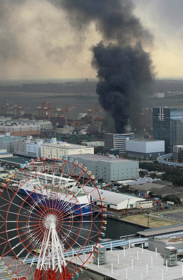 Photo - Black smoke rises from a burning building in Tokyo after Japan was struck by a magnitude 8.9 earthquake off its northeastern coast Friday, March 11, 2011. (AP Photo/Kyodo News) JAPAN OUT, MANDATORY CREDIT, FOR COMMERCIAL USE ONLY IN NORTH AMERICA ORG XMIT: TOK808