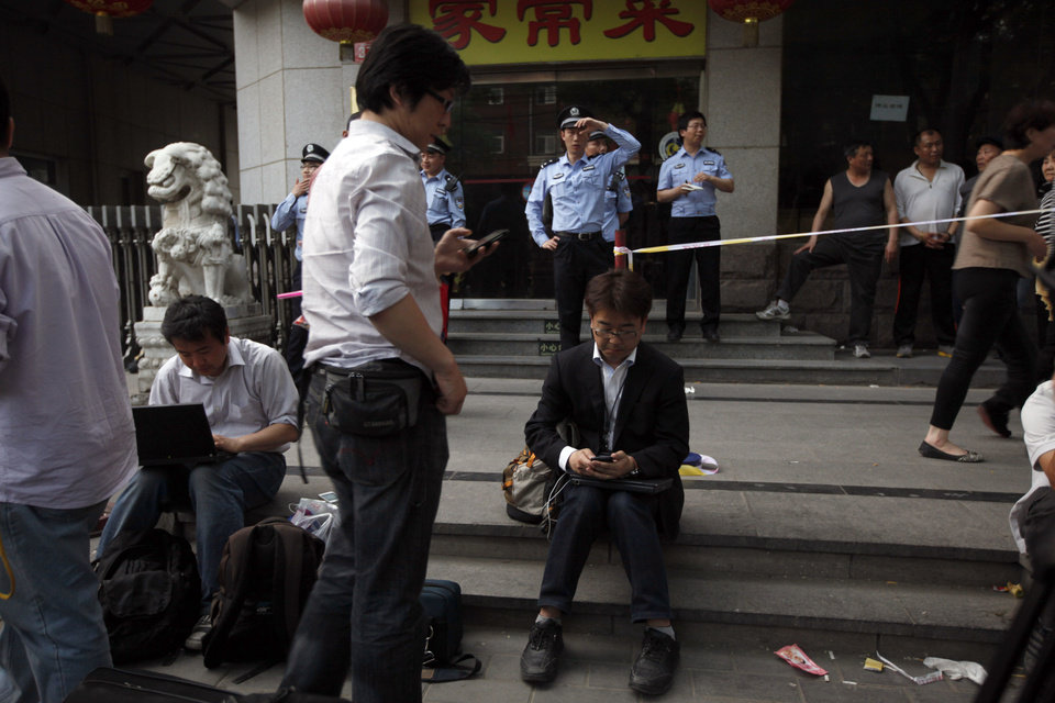 Photo -   Chinese police officers watch over journalists outside the hospital where blind Chinese activist Chen Guangcheng is recuperating in Beijing, China, Thursday, May 3, 2012. U.S. officials said Thursday they are still trying to help Chen who says he fears for his family's safety, and denied he was pressured to leave the American Embassy to resettle inside China.(AP Photo/Ng Han Guan)