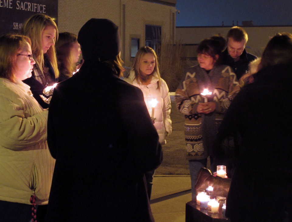 CORRECTS SOURCE TO ASSOCIATED PRESS, NOT TOPEKA CAPITOL JOURNAL - People gather for a small candlelight vigil on Sunday, Dec. 16, 2012, at the Law Enforcement Center in Topeka, Kan. Two Kansas police officers were shot outside the store on Sunday while responding to a report of a suspicious vehicle and died later at a hospital, authorities said. (AP Photo/John Hanna)