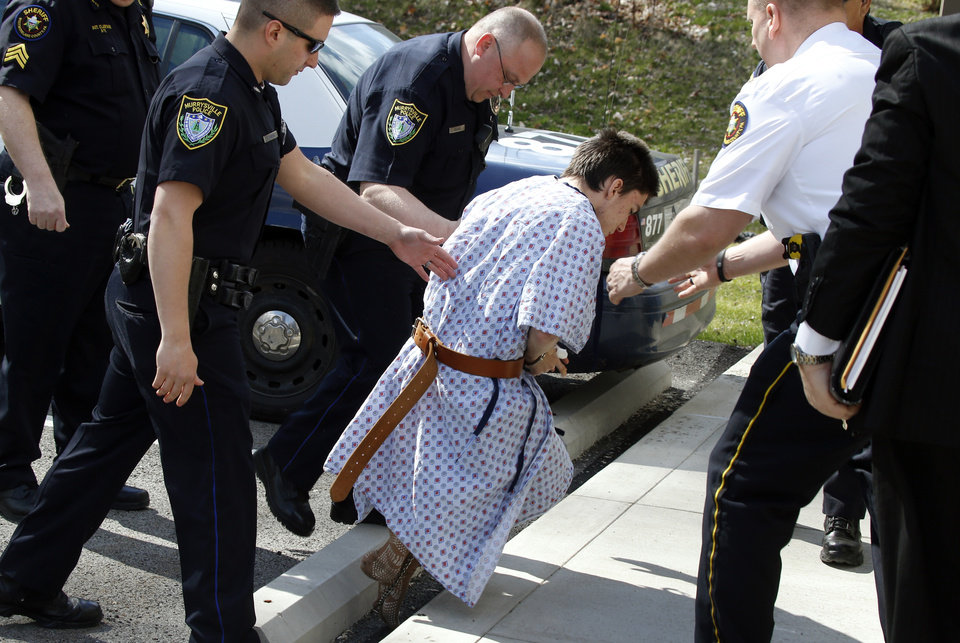 Photo - Alex Hribal, the suspect in the multiple stabbings at the Franklin Regional High School in Murrysville, Pa., stumbles as he is escorted by police to a district magistrate to be arraigned on Wednesday, April 9, 2014, in Export, Pa. Authorities say Hribal has been charged after allegedly stabbing and slashing at least 19 people, mostly students, in the crowded halls of his suburban Pittsburgh high school Wednesday. (AP Photo/Keith Srakocic)