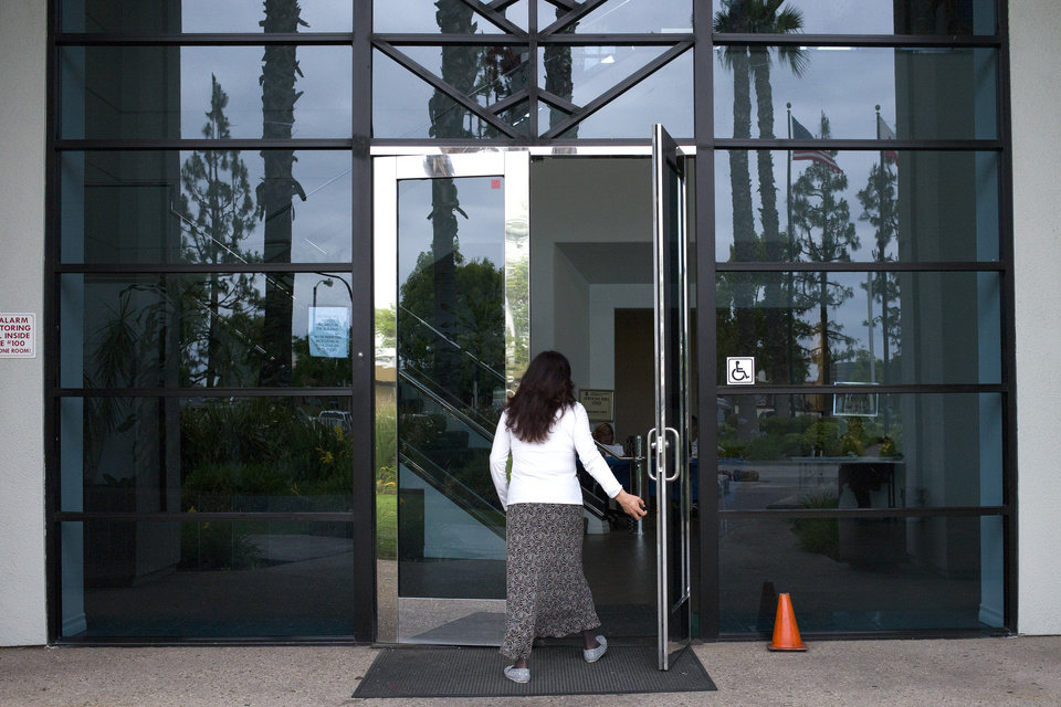 Photo - A woman enters a Los Angeles County Department of Children and Family Services building, where kidnapping suspect Isidro Garcia worked as a janitor, on Thursday, May 22, 2014, in Commerce, Calif. A California woman who says she was kidnapped a decade ago by her mother's boyfriend lived a seemingly ordinary life with her alleged captor year after year, but was too scared to go to authorities until she recently reunited with her mother, police said Thursday. (AP Photo/Jae C. Hong)