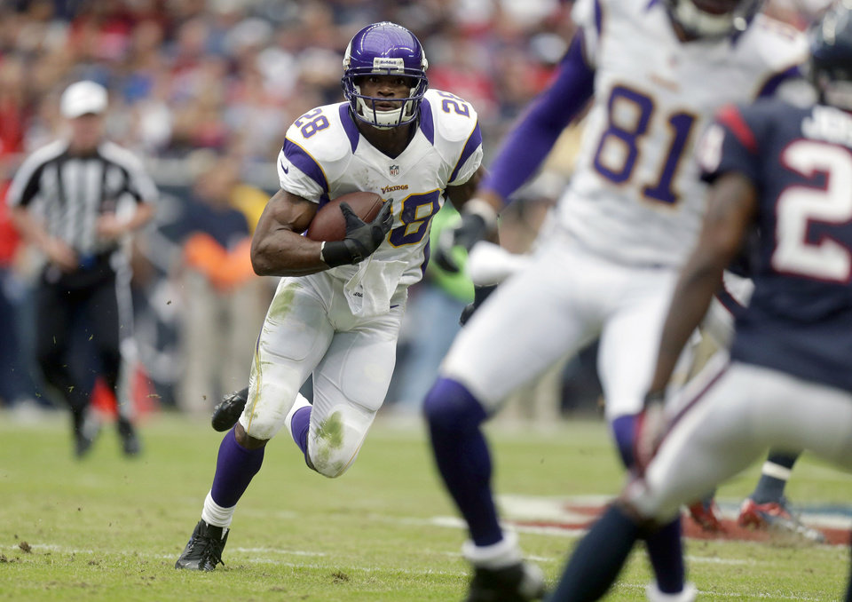 Photo - Minnesota Vikings running back Adrian Peterson (28) rushes for a gain during the first quarter of an NFL football game against the Houston Texans, Sunday, Dec. 23, 2012, in Houston. (AP Photo/Patric Schneider)