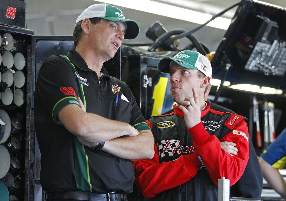 Photo -   Regan Smith, right, talks with crew cheif Steve Letarte, left, before practice for Saturday's NASCAR Bank of America 500 Sprint Cup series auto race in Concord, N.C., Thursday, Oct. 11, 2012. Smith is replacing driver Dale Earnhardt Jr, who is sitting out the next two races due to a concussion. (AP Photo/Chuck Burton)