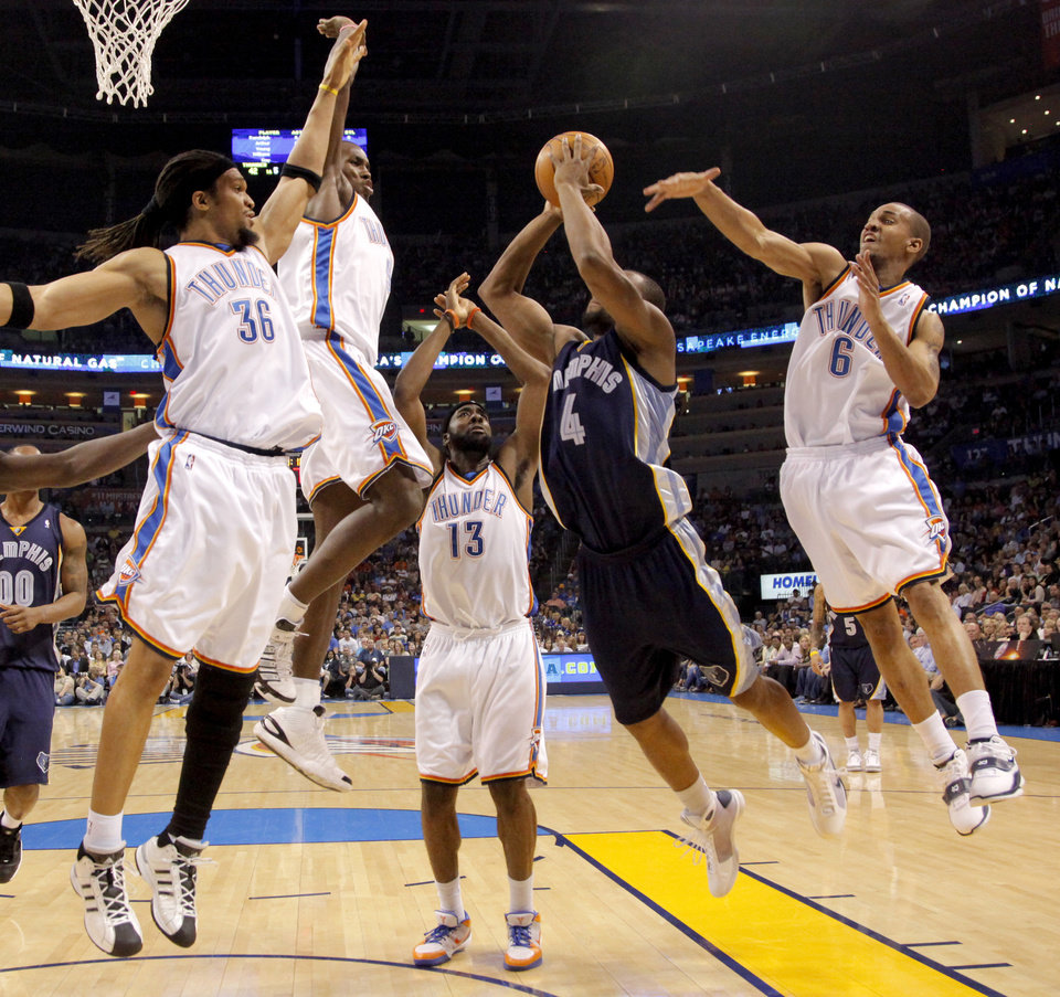 Photo - Oklahoma City's Etan Thomas, left, Serge Ibaka, James Harden, and Eric Maynor defend Sam Young of Memphis during the NBA basketball game between the Oklahoma City Thunder and the Memphis Grizzlies at the Ford Center in Oklahoma City on Wednesday, April 14, 2010. 