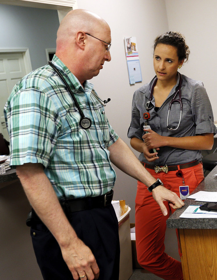 Photo - Dr. Dennis Carter talks with fourth-year medical student Tiffany Palmer at  Carter's office in Poteau on June 13. Palmer is working with Carter for the summer. Photo by Nate Billings, The Oklahoman  NATE BILLINGS - NATE BILLINGS