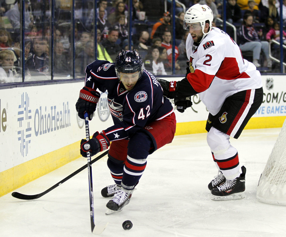 Photo - Columbus Blue Jackets' Artem Anisimov, left, of Russia moves the puck against Ottawa Senators' Jared Cowen in the second period of an NHL hockey game in Columbus, Ohio, Tuesday, Nov.5, 2013. (AP Photo/Paul Vernon)
