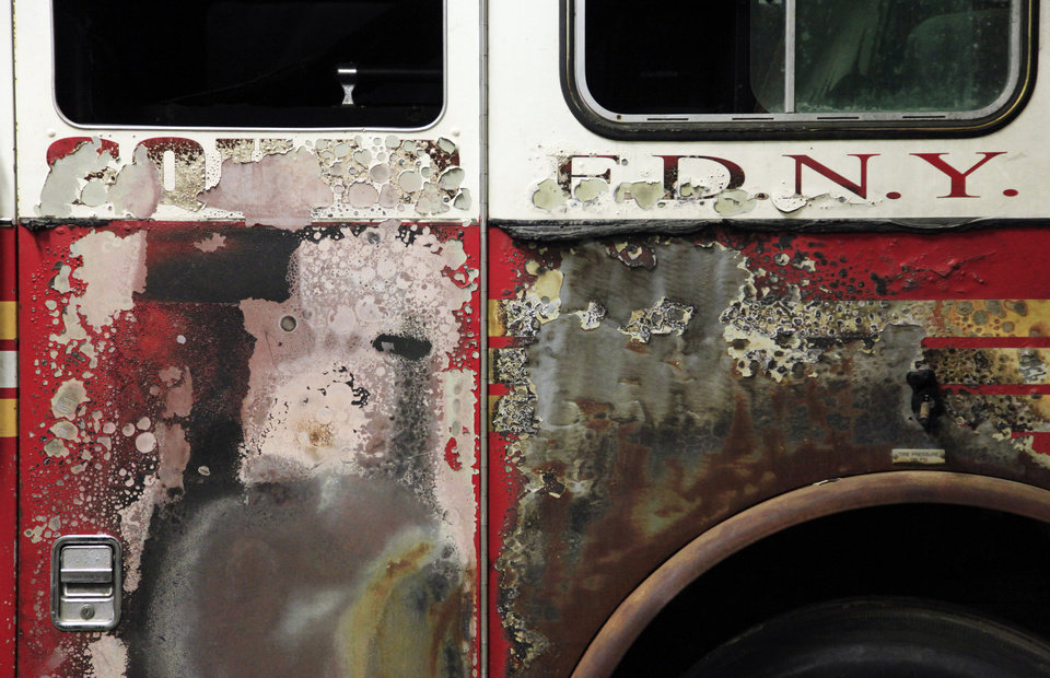 Photo - FILE - This June 16, 2011 file photo shows a fire-scorched cab of a New York City Fire Department truck, damaged in the attacks of Sept. 11, 2001, in storage at JFK Airport in New York. The truck will be on display in the 9//11 museum that will be dedicated Thursday, May 15, 2014, in a ceremony attended by President Barack Obama. It will open to the public May 21. (AP Photo/Mark Lennihan, File)