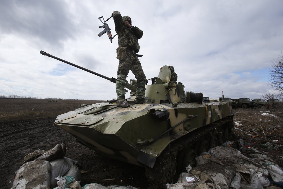 Photo - A Ukrainian soldier stands atop an armored vehicle at a military camp near the village of Michurino, Ukraine, Monday, March 17, 2014. Addressing lawmakers in Ukraine's parliament on Monday, Olexandr Turchynov, the acting president, described Sunday's Crimean poll as a farce that would