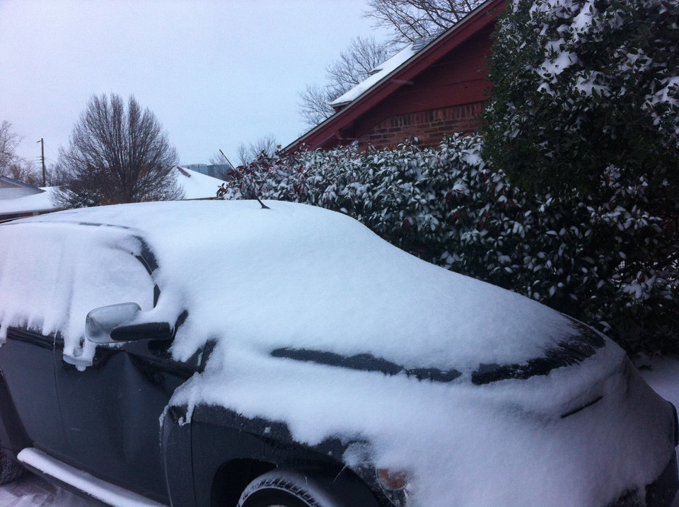 Photo - A car covered in snow Friday morning in Oklahoma City - Photo by Robert Medley