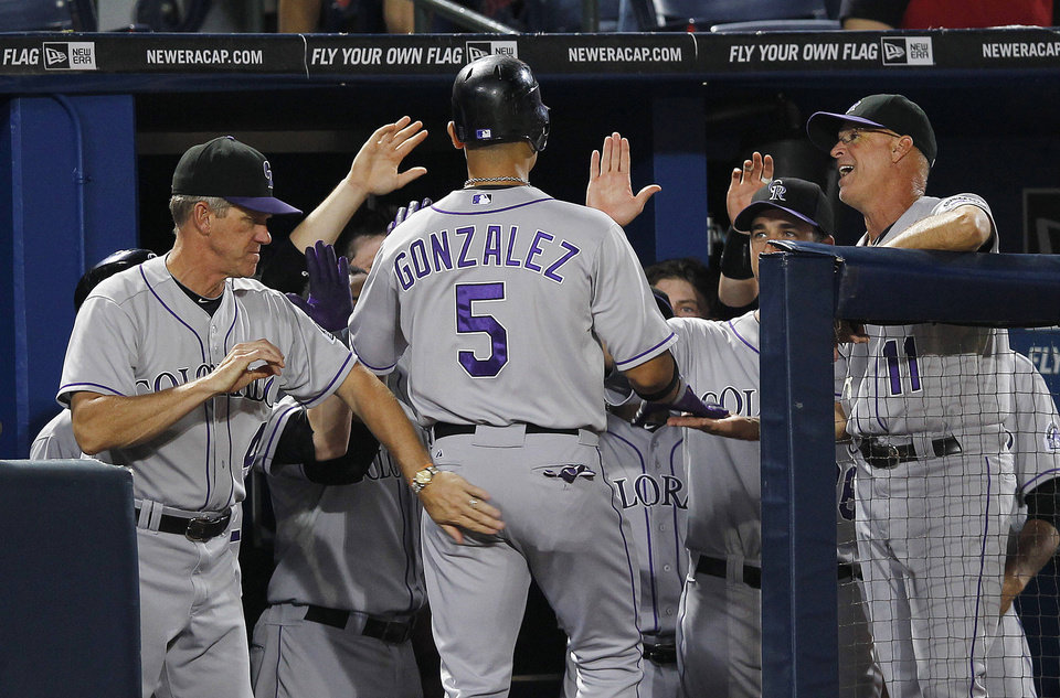 Photo -   Colorado Rockies' Carlos Gonzalez (5) is greeted by manager Jim Tracy, left, and bench coach Tom Runnells (11) after hitting a solo home run in the fourth inning of a baseball game against the Atlanta Braves on Tuesday, Sept. 4, 2012, in Atlanta. (AP Photo/John Bazemore)