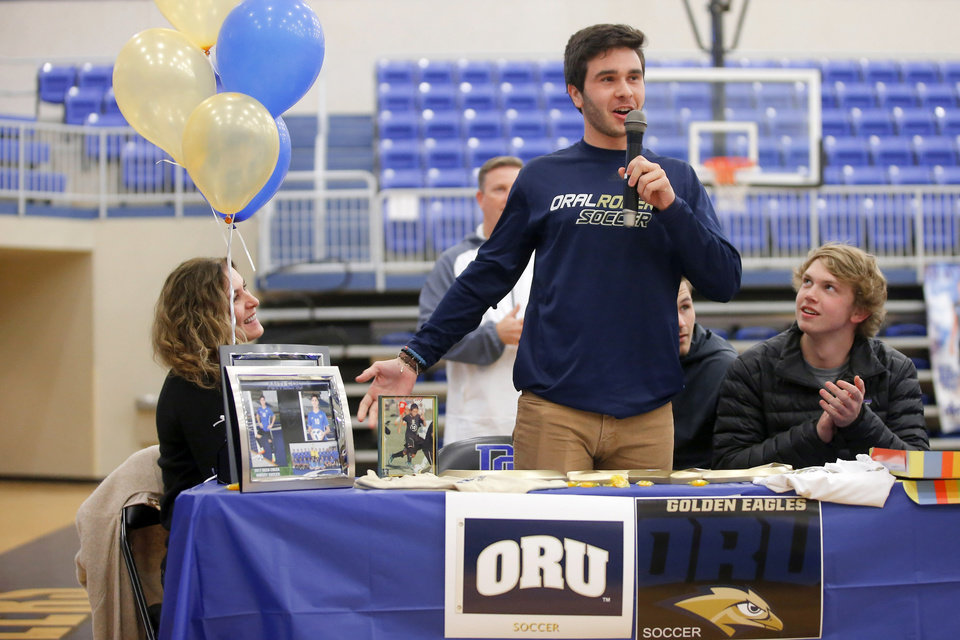 Photo - Deer Creek soccer player Chris Smirlis  speaks before signing a letter of intent to play soccer at Oral Roberts University as his mother, Anastasia Smirlis, left and Matthew Loftis listen during a signing day ceremony at Deer Creek High School, Wednesday, Feb. 7, 2018.  Photo by Bryan Terry, The Oklahoman