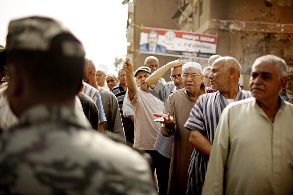 Photo -   Egyptian voters argue with a solider as they wait cast ballots in Basateen a southern suburb of Cario, Egypt on Wednesday, May 23, 2012. On Wednesday morning, Egypt commenced two days of presidential voting after 16 months of interim rule by the Supreme Council of Armed Forces. This election is the first free and fair presidential race since the ouster of former President Hosni Mubarak. (AP Photo/Pete Muller)