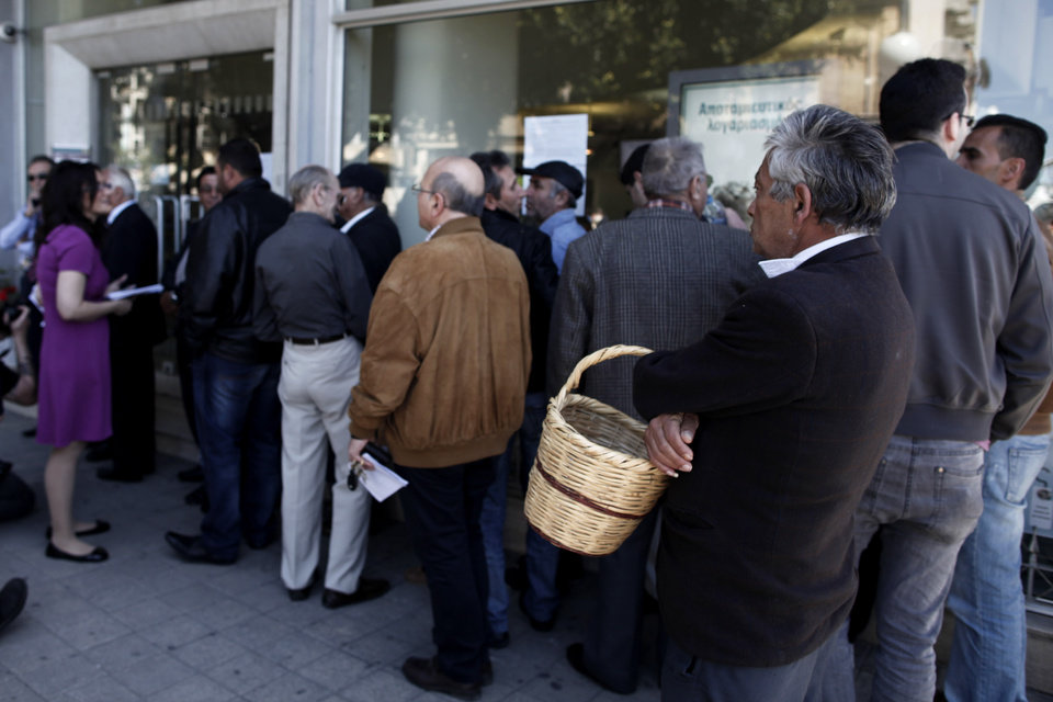 Photo - People wait in line to enter a branch of the Bank of Cyprus in Nicosia, Thursday, March 28, 2013. Banks in Cyprus reopened to customers for the first time in nearly two weeks Thursday, albeit with strict restrictions on transactions, after being closed to prevent people withdrawing all their savings during the country's acute financial crisis. Large lines had formed outside the banks ahead of the opening of banks for six hours from noon. (AP Photo/Petros Giannakouris)