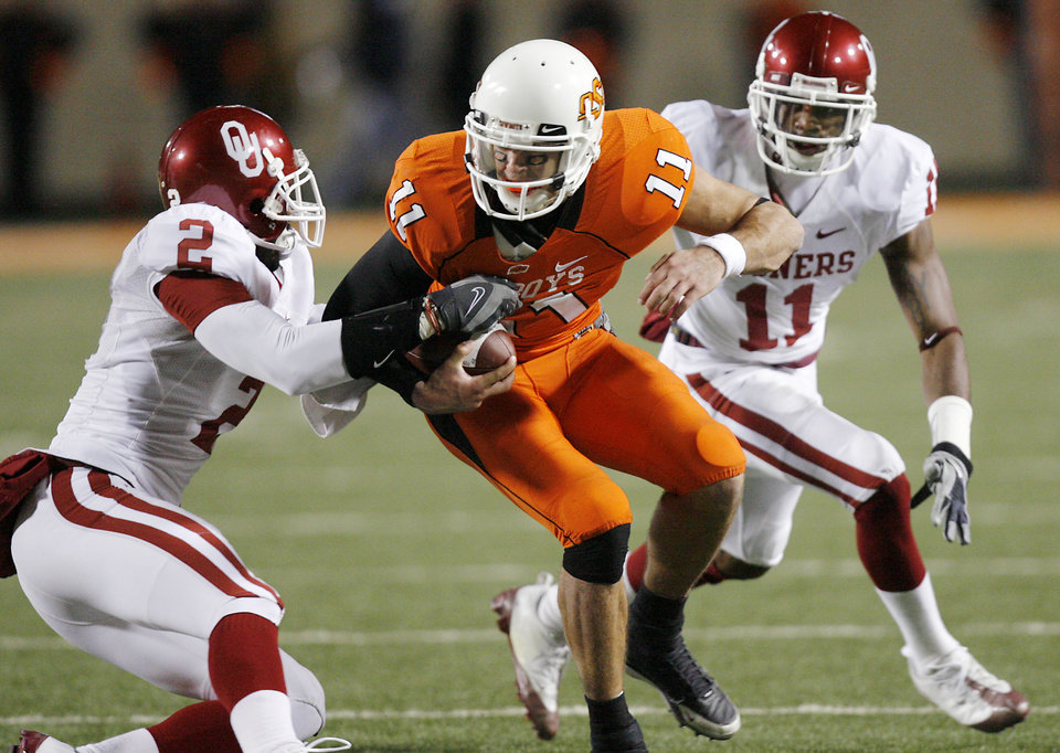 Oklahoma State\'s Zac Robinson (11) is brought down by Oklahoma\'s Brian Jackson (2) and Lendy Holmes (11) during the second half of the college football game between the University of Oklahoma Sooners (OU) and Oklahoma State University Cowboys (OSU) at Boone Pickens Stadium on Saturday, Nov. 29, 2008, in Stillwater, Okla. STAFF PHOTO BY CHRIS LANDSBERGER