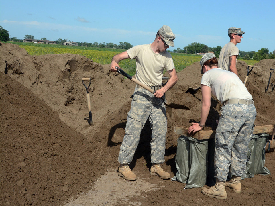 Photo - Soldiers from the South Dakota National Guard fill sandbags, Thursday, June 19, 2014, at Dakota Valley Elementary School across from McCook Lake in North Sioux City, S.D.  Cities in Iowa, Nebraska, and South Dakota are fighting a surging Big Sioux River after heavy rain this week pushed the waterway to record levels in some locations. (AP Photo/Dirk Lammers)