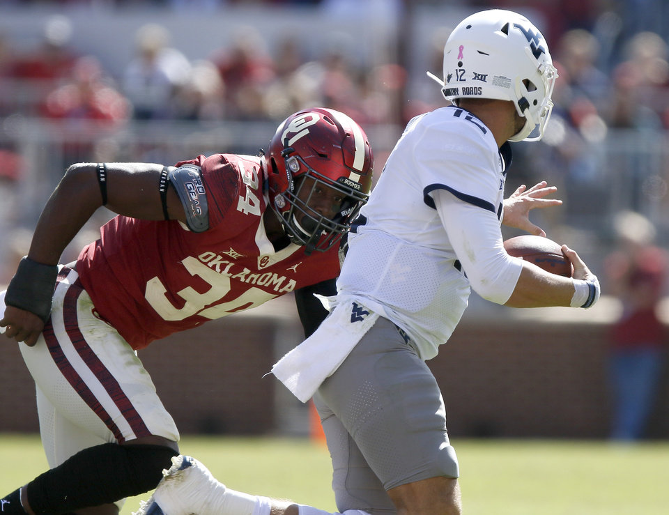 Photo - Oklahoma's Brian Asamoah (24) runs after West Virginia's Austin Kendall (12) during a college football game between the University of Oklahoma Sooners (OU) and the West Virginia Mountaineers at Gaylord Family-Oklahoma Memorial Stadium in Norman, Okla, Saturday, Oct. 19, 2019. Oklahoma won 52-14. [Bryan Terry/The Oklahoman]
