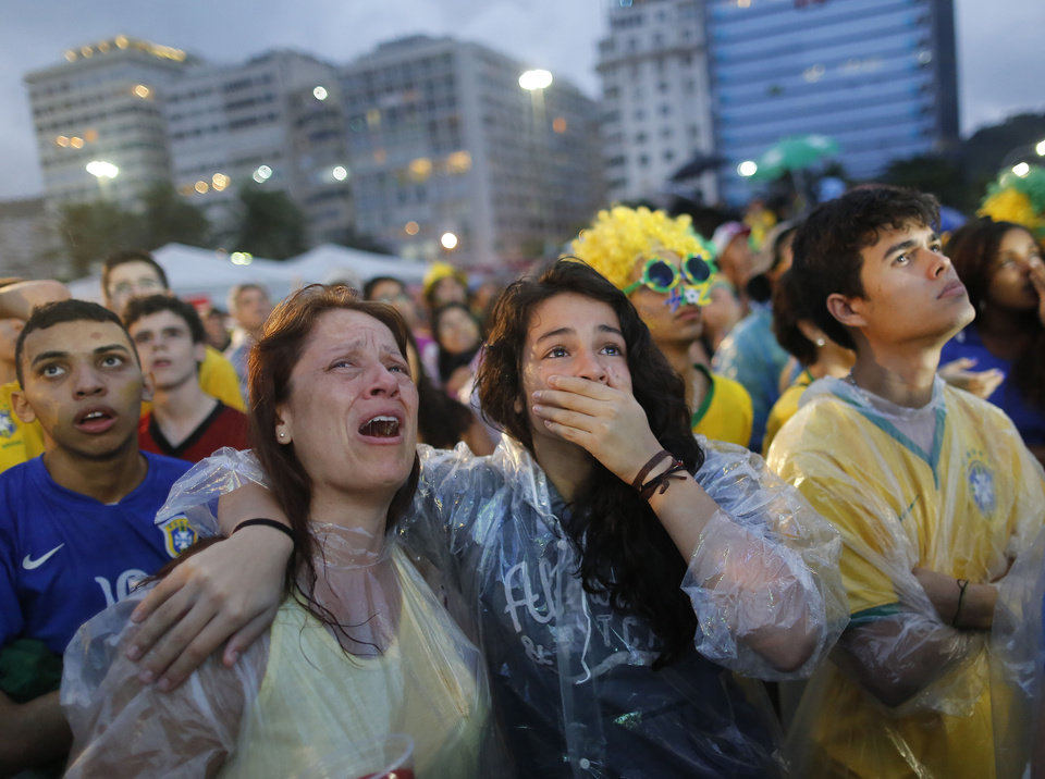 Photo - Brazil soccer fans cry as they watch their team play a World Cup semifinal match against Germany on a live telecast inside the FIFA Fan Fest area on Copacabana beach in Rio de Janeiro, Brazil, Tuesday, July 8, 2014. (AP Photo/Leo Correa)