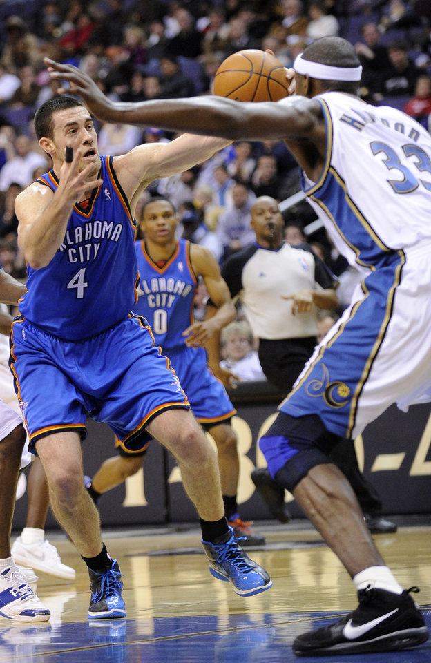 Photo - Oklahoma City Thunder forward Nick Collison (4) tries to control the ball against Washington Wizards center Brendan Haywood (33) during the first half of an NBA basketball game Tuesday, Dec. 29, 2009, in Washington. The Thunder won 110-98. (AP Photo/Nick Wass)