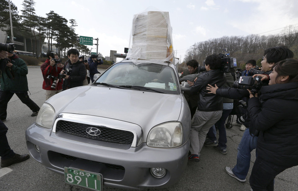 Photo - A South Korean vehicle with products from North Korea's Kaesong is surrounded by media upon its arrival at the customs, immigration and quarantine office near the border village of Panmunjom, which has separated the two Koreas since the Korean War, in Paju, north of Seoul, South Korea, Tuesday, April 9, 2013. North Korean workers didn't show up for work at a jointly run factory complex with South Korea on Tuesday, a day after Pyongyang suspended operations at the last remaining major economic link between rivals locked in an increasingly hostile relationship. (AP Photo/Lee Jin-man)